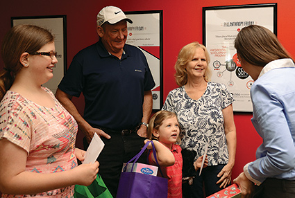 Left to right, Haley Gibson, Gene Hynes, Charlotte Gibson and Mary Ann Hines meet in the UNM Foundation lobby to receive a few gifts for Charlotte in appreciation of the family's generosity and Charlotte's courage. Photo: Natch Anan